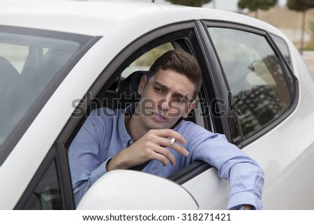Young man looking outside from his car while smoking a cigarette