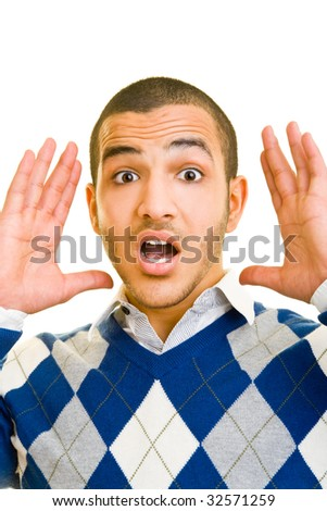 Young man looking surprised into the camera - stock photo