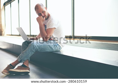 Young man looking thoughtful while working on laptop computer holding it on the knees, university student using notebook for write his coursework, freelancer sitting in modern interior thinking about