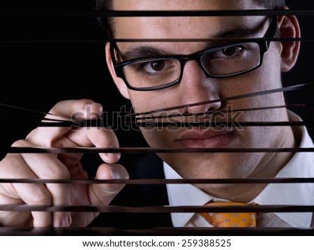 Young man looking through a window blind - stock photo
