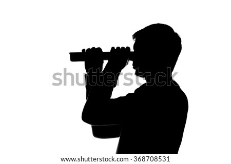 Young man looking through curled paper, a sheet of paper, the telescope - a dark silhouette