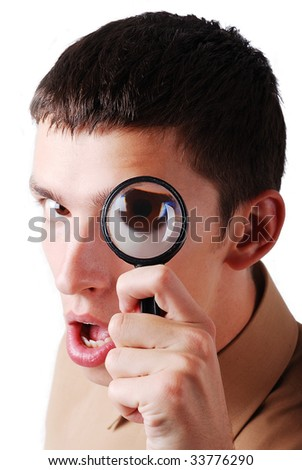 Young man looking through magnifier