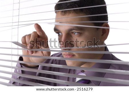 Young man looking through the blind. White background in studio. - stock photo
