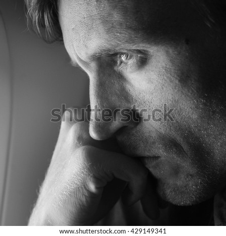 Young man looking through window in airplane.