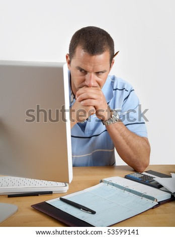 Young man looking tired, frustrated and worried as he sits at his desk with computer, checkbook and calculator. - stock photo