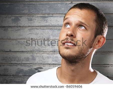 young man looking up against a grunge background - stock photo