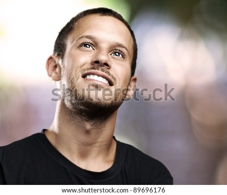 young man looking up and smiling at house - stock photo