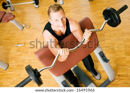 Young man (looking up) having a training session in the gym using a barbell - stock photo