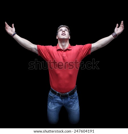 Young man looking up in a kneeling position with raised hands - stock photo