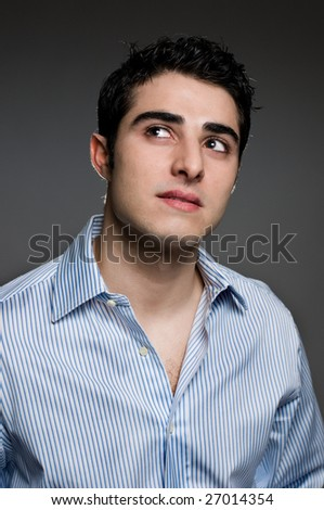 Young man looking up in a thoughtful expression, fine art portrait. Real people portraiture