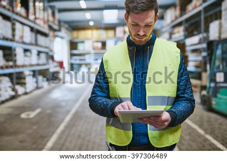 Young man looking up order details on a tablet as he shops in a hardware warehouse for supplies , close up upper body - stock photo