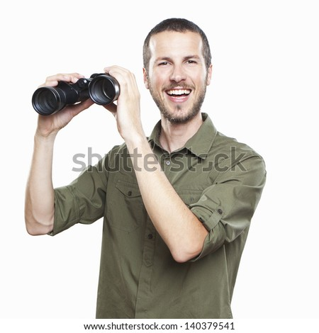 young man looking with binoculars, cheerful face expression - stock photo