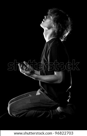 Young man looks up in prayer - stock photo