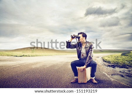 young man looks with binoculars sitting on a suitcase in the middle of a deserted road - stock photo