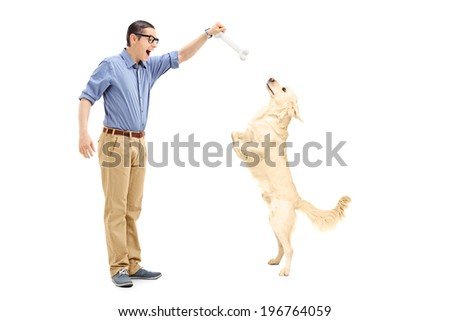 Young man luring a dog with a bone isolated on white background - stock photo