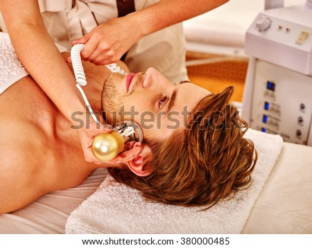 Young man luxuriating on electroporation  facial therapy at beauty salon.  - stock photo