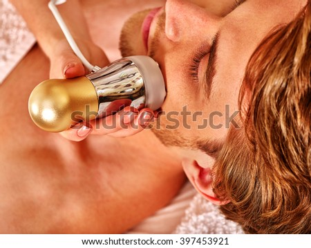 Young man luxuriating on electroporation  facial therapy at beauty salon. Modern technologies. - stock photo