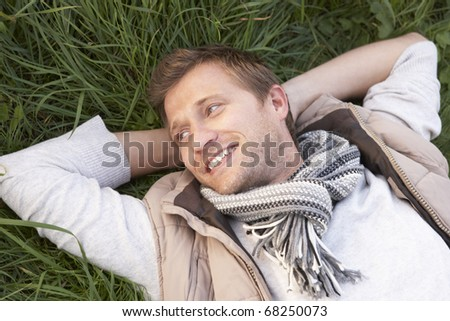 Young man lying alone on grass - stock photo