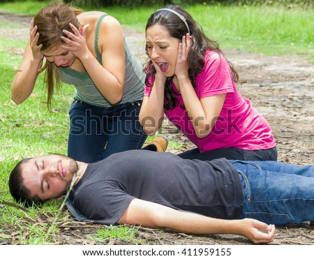 Young man lying down with medical emergency, two young women acting hysterically, outdoors environment - stock photo