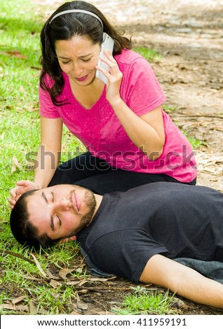 Young man lying down with medical emergency, woman sitting by his side calling for help, outdoors environment - stock photo