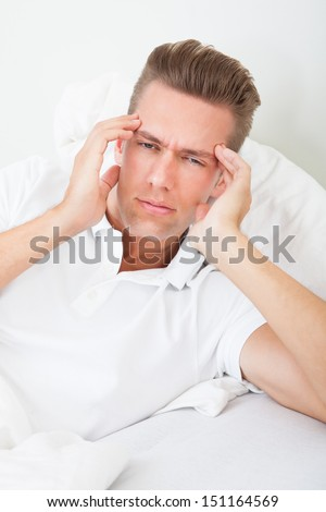 Young Man Lying On Bed Suffering From Headache - stock photo