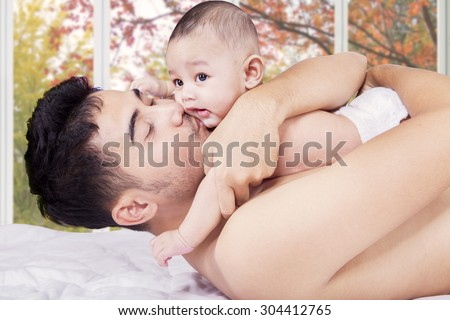 Young man lying on bed while holding and kiss his little baby, shot at home