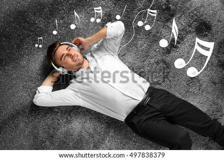Young man lying on carpet and enjoying music. Notes on gray textured background.