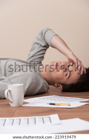 young man lying on floor and looking into camera. tired guy resting with documents and cup on wooden floor - stock photo