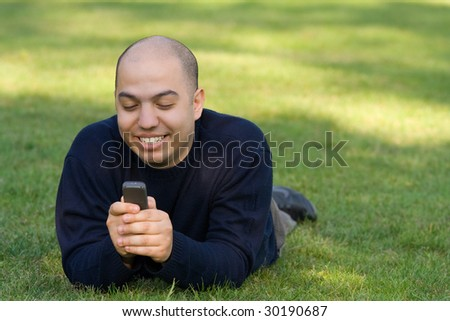 Young man lying on grass and messaging on the mobile phone - stock photo