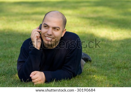 Young man lying on grass and talking on the mobile phone - stock photo