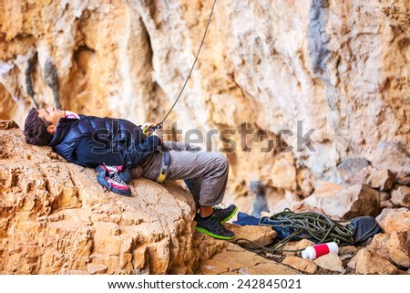 Young man lying on stone and watching leading rock climber while belaying