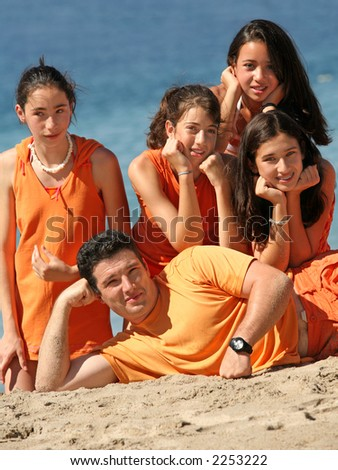 Young man lying on the beach with his daughter and her girlfriends - stock photo