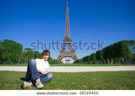 Young man lying on the Champs de Mars. Eiffel tower in background - stock photo