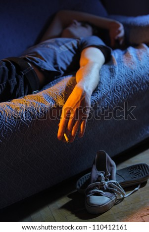 Young man lying on the couch smoking a joint - stock photo