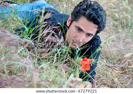 young man, lying on the grass looking at flower - stock photo