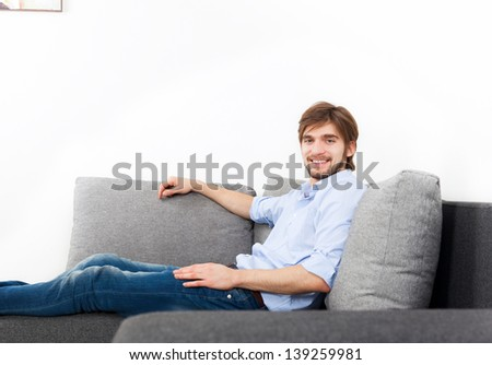 young man lying relaxing on the couch, sofa home indoors, happy smile looking at camera, with copy space on white wall