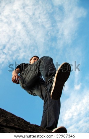 young man make a pace from the stone edge, blue sky and cloudscape background - stock photo