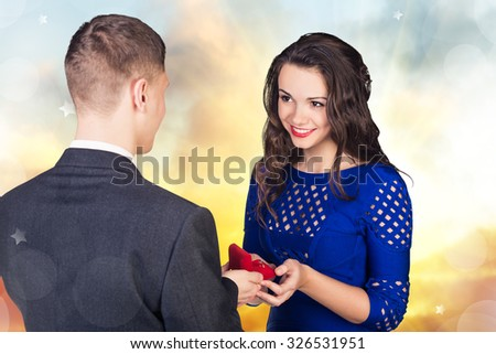 Young man makes a proposal to his girlfriend on the autumn colors background