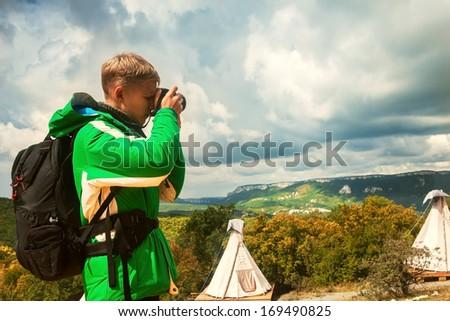 Young man makes outdoor shots on mountain plato - stock photo
