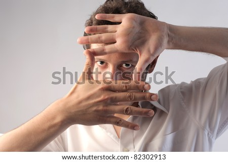 Young man making a frame with his hands - stock photo