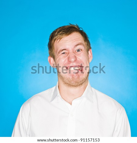 Young man making a funny face on blue background