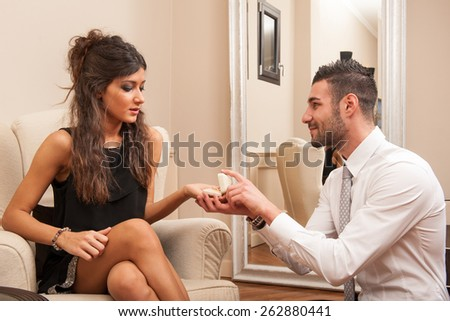 Young man making a marriage proposal offering ring to his girlfriend in hotel. - stock photo