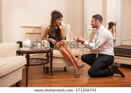 Young man making a marriage proposal to his girlfriend in hotel.