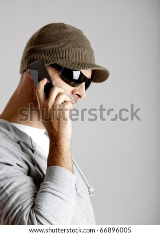 Young man making a phone call with a cellphone - stock photo