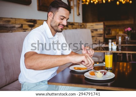 Young man making a toast at the cafe - stock photo