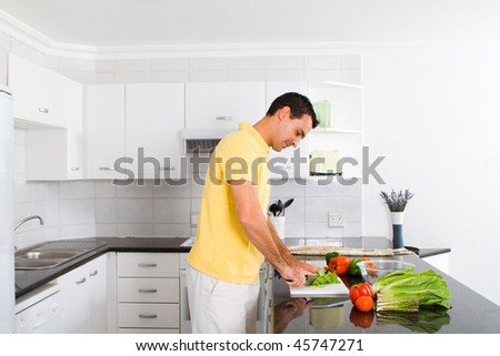 young man making healthy salad in modern kitchen - stock photo