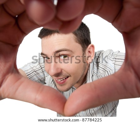 young man making heart sign on wide angle studio shot - stock photo