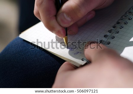 Young man making notes in the notepad on the street
