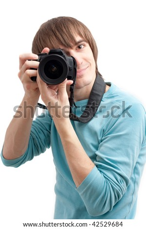 Young man making photo with professional camera. Over white - stock photo