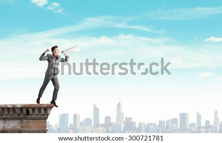 Young man making some announcement in trumpet - stock photo